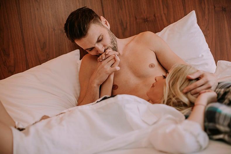Par ligger i sengen og slapper af