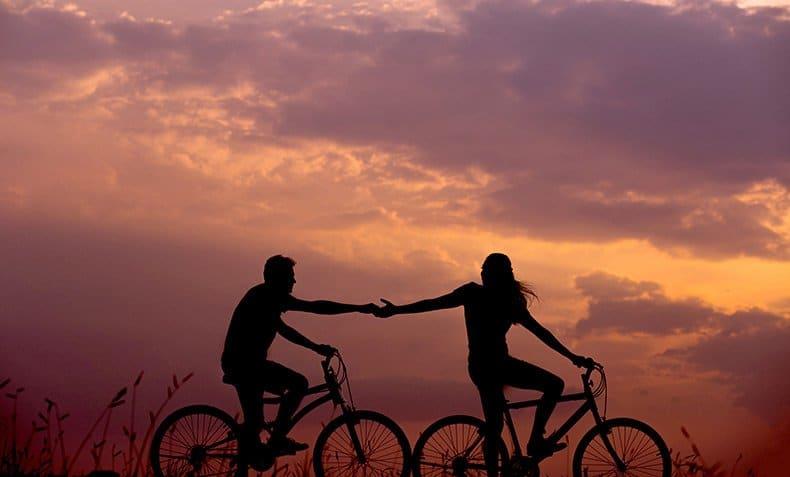 Par på cykel i solnedgang